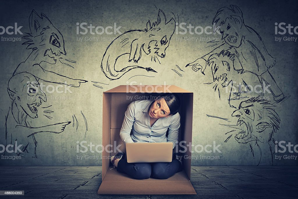 Evil men pointing at stressed woman sitting in a box stock photo