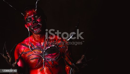 Evil or devil listening music by using earphones in darkness. Demon gets happy and closing eyes. Monster love listening nice song. It looks funny. Monster skin is red. Satan come from hell. copy space