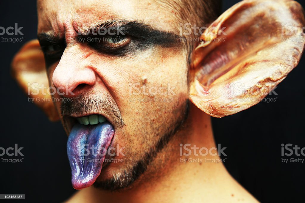 Evil Portrait of Goblin Man With Blue Tongue stock photo
