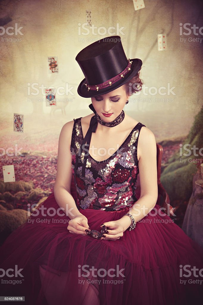 Evil Queen in bowler looking on the clocks stock photo