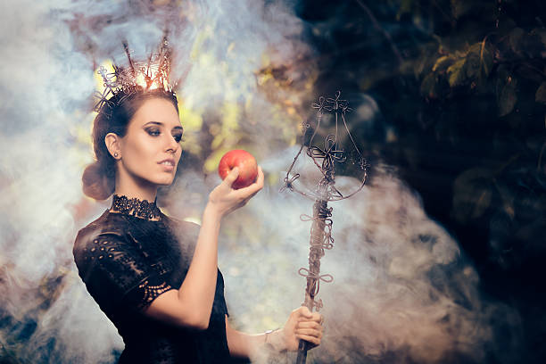 evil queen with poisoned  apple in misty forest - 白雪姫 ストックフォトと画像