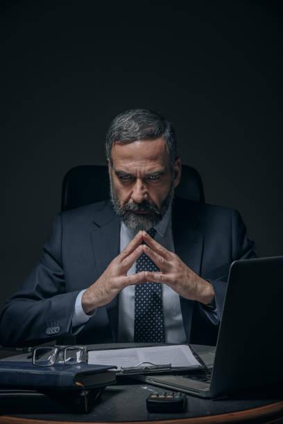 Evil senior business man stock photo