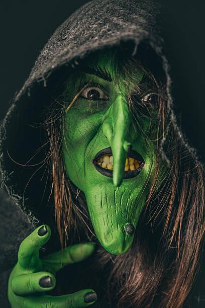 Evil witch casting a curse under her hood - foto de stock