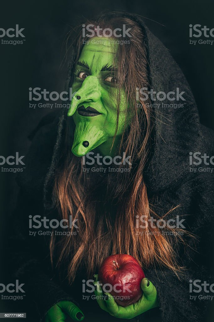 Evil witch holding a rotten apple - foto de stock