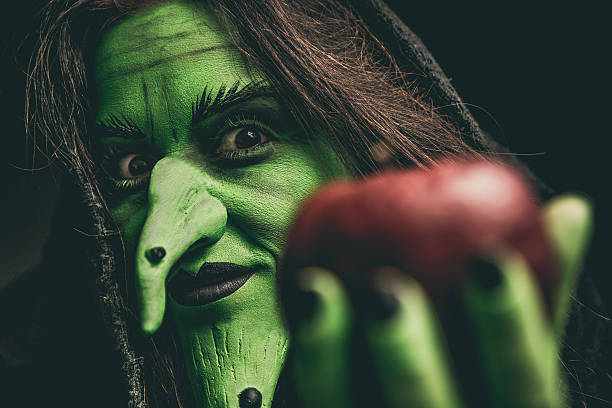 Evil witch looking at camera holding a red apple - foto de stock