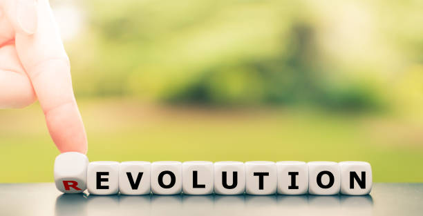 """Evolution instead of revolution. Hand turns a dice and changes the word """"revolution"""" to """"evolution"""". stock photo"""