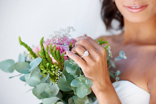Exactly the way she wanted her wedding A beautiful young bride looking at her bridal bouquet ring jewelry stock pictures, royalty-free photos & images