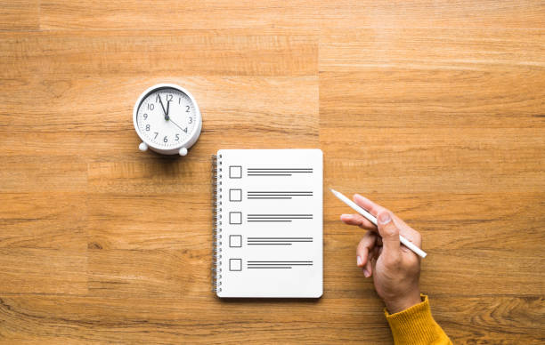 Exam and time management concepts with male hand holding pencil and paper sheet on table Exam and time management concepts with male hand holding pencil and paper sheet on wood table. checklist stock pictures, royalty-free photos & images