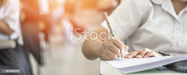 963192098 istock photo Exam at school with student's taking educational admission test in class, thinking hard, writing answer in university classroom, education and world literacy day concept 1180689032