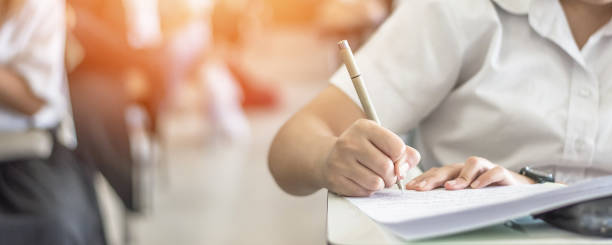 Exam at school with student's taking educational admission test in class, thinking hard, writing answer in university classroom, education and world literacy day concept stock photo