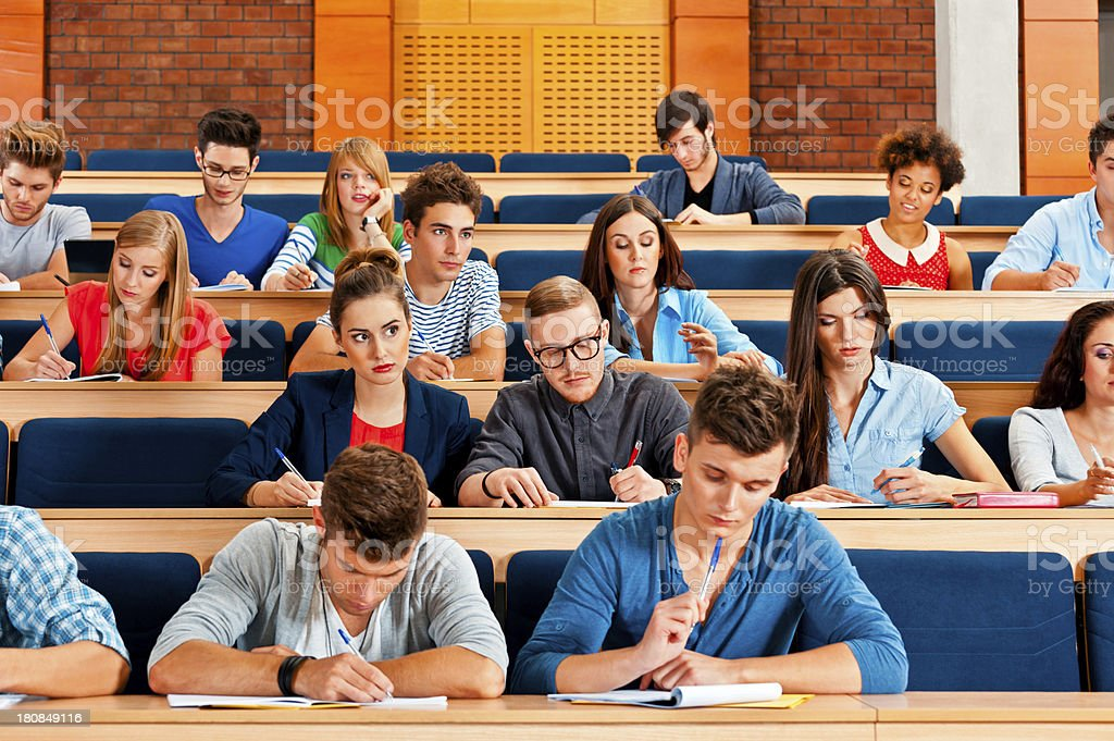 Exam at the university Large group of college students sitting in the lecture hall at university and writing an exam. 20-24 Years Stock Photo