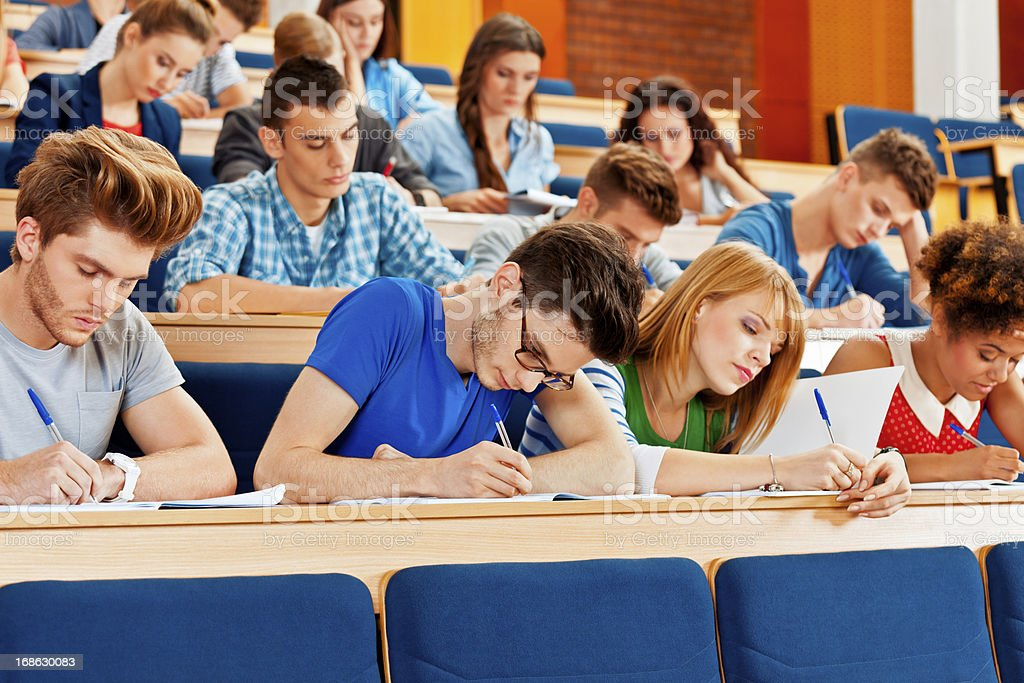 Exam at the univertisty Large group of high school students sitting in the lecture hall at university and writting an exam. 20-24 Years Stock Photo