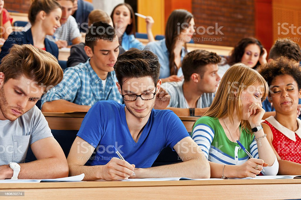Large group of college students sitting in the lecture hall and...