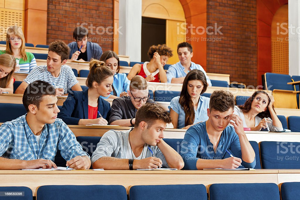Exam Large group of high school students sitting in the lecture hall at university and writting an exam. 20-24 Years Stock Photo