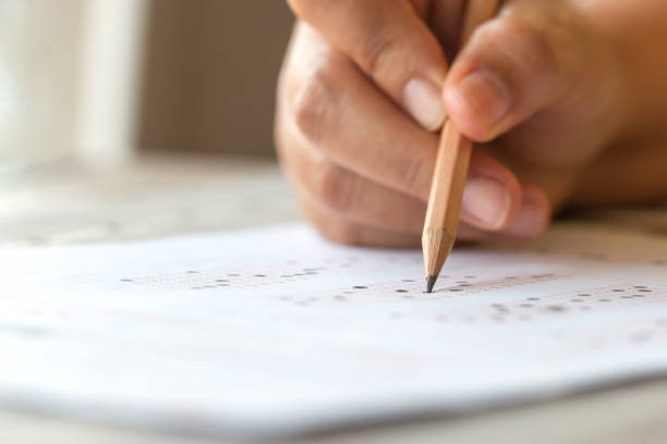 Exam test school or university concept : Hand student holding pencil writing standardized answer multiple carbon paper form with gray black answers sheet bubbled of question in examination assessment. stock photo