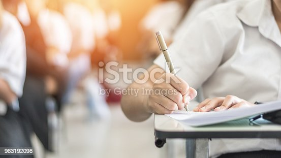 istock Exam with school student having a educational test, thinking hard, writing answer in classroom for  university education admission and world literacy day concept 963192098