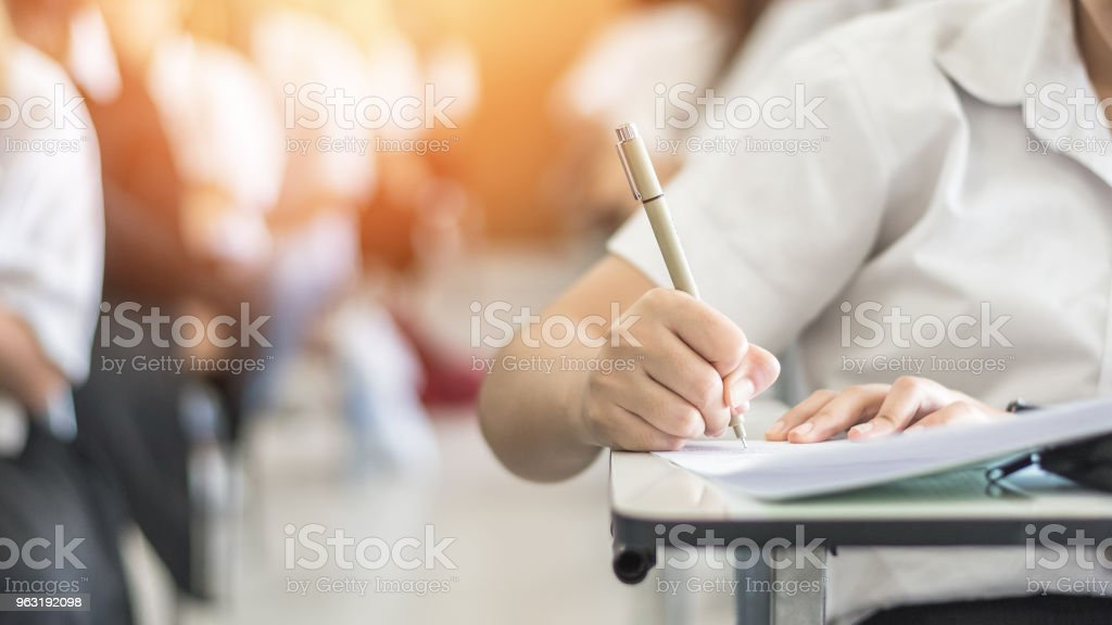 Exam with school student having a educational test, thinking hard, writing answer in classroom for  university education admission and world literacy day concept stock photo