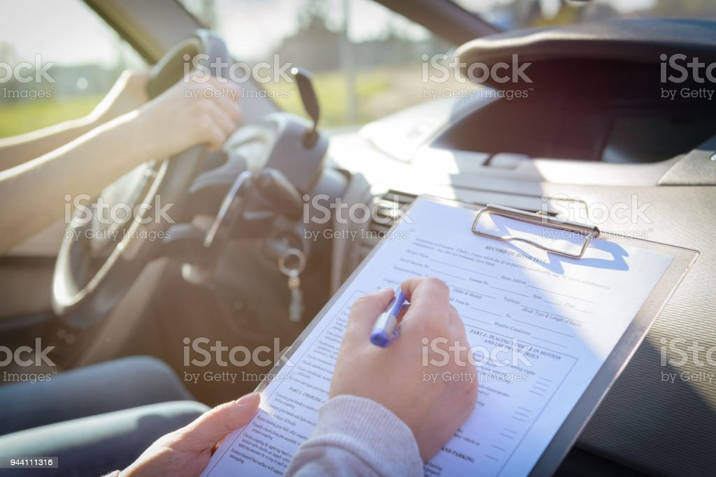 Examiner filling in driver's license road test form stock photo