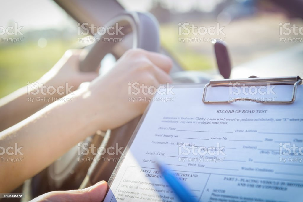 Examiner Filling In Drivers License Road Test Form Stock