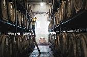 Caucasian adult man examining barrel in distillery.