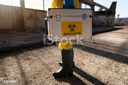 Cut out man in protective workwear examining radioactive ruined building.