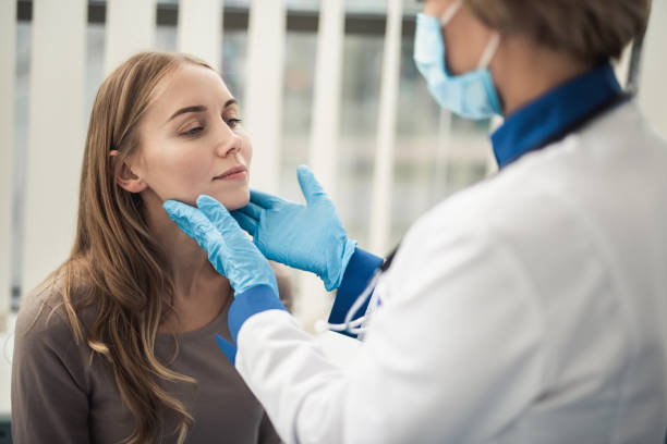 Examining of female patient in medical cabinet Concept of professional consultation in therapist system. Close up portrait of doctor woman examining tonsils of smiling young lady in medical office throat stock pictures, royalty-free photos & images
