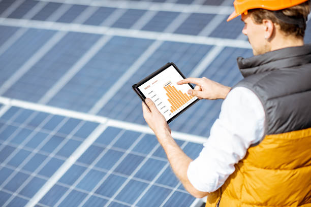 Examining production of solar power plant with digital tablet stock photo