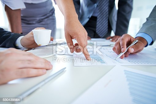 Hands of business people pointing at statistical data