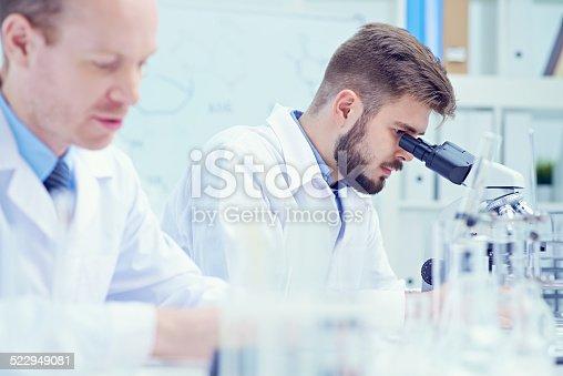 istock examining virus through microscope 522949081