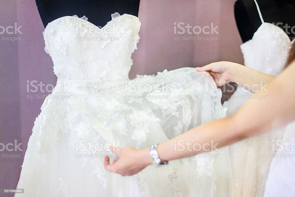 Examining wedding dress stock photo