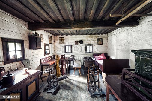 Inside of an old farmhouse with hardwood flooring and ceiling, traditional wooden furniture (chair, benches, chest, spinning wheels etc.) and rustic tiled bread oven.