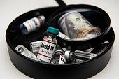 istock Example of coronavirus vaccine. Glass needle ampoules, syringe and 100 dollar bill 1332008225