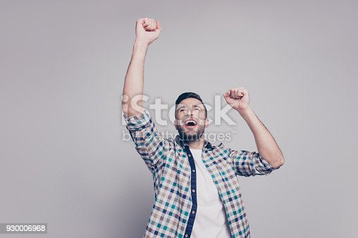 1092211952 istock photo Exams handed over. Happy brunet guy with bristle in casual checkered shirt celebrating victory with his raised cams, laughing with beaming smile over grey background 930006968
