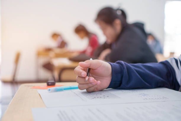 exams test student in high school, university student holding pencil for testing exam writing answer sheet and exercise for taking in assessment paper on wood table classroom. education study concept - exam stock pictures, royalty-free photos & images