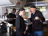 Exasperated chef scolding female employee