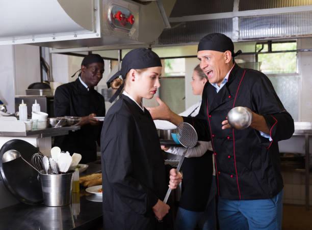 exasperated chef scolding female employee - chef triste foto e immagini stock