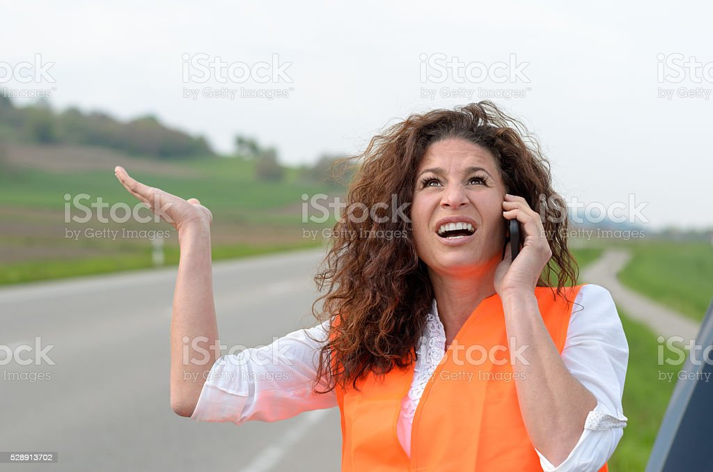 Exasperated young female driver on her mobile stock photo