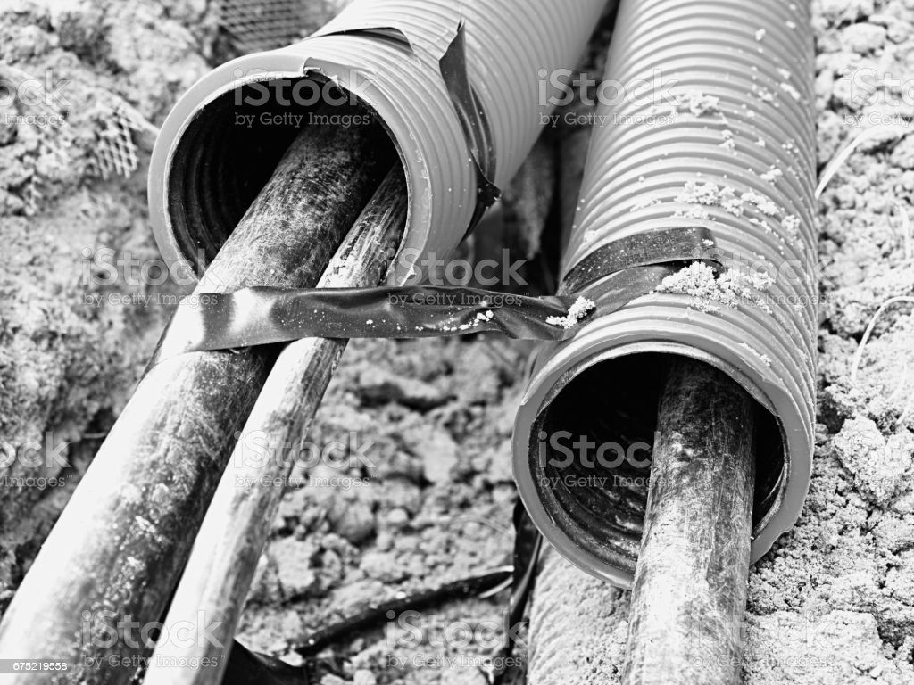 Excavation of trench  with black cables in protective HDPE tube. Lines of metallic and fiber optic wires. royalty-free stock photo
