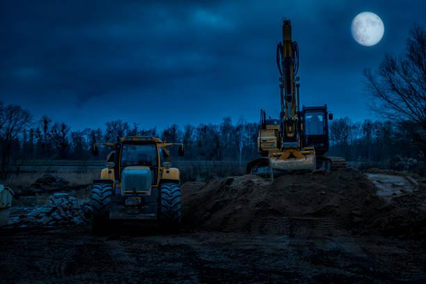 Bagger und LKW bei Mondlicht – Foto
