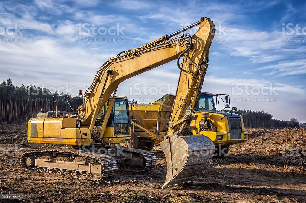 Excavator and dump truck on a new road construction stock photo