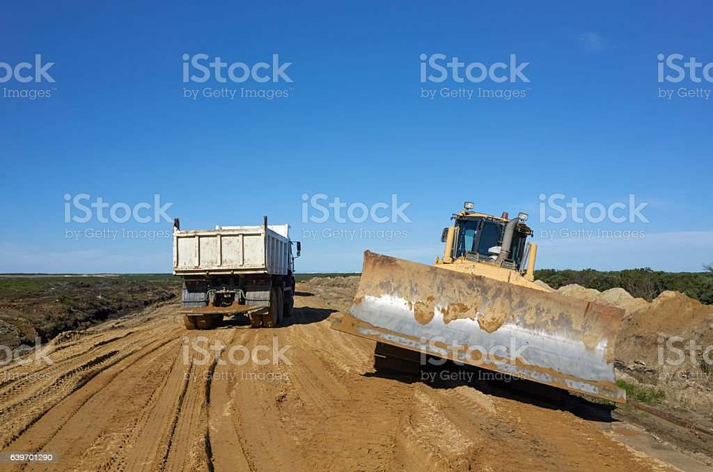 Excavator and dumper make a new road stock photo