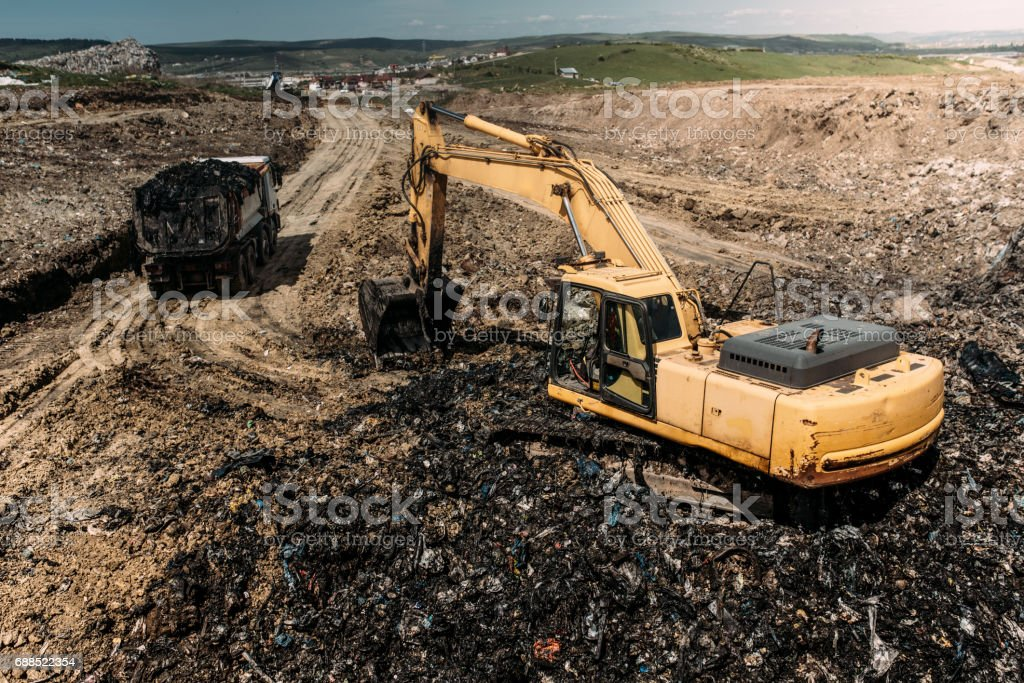 Excavator and dumper truck working on modern garbage construction site stock photo