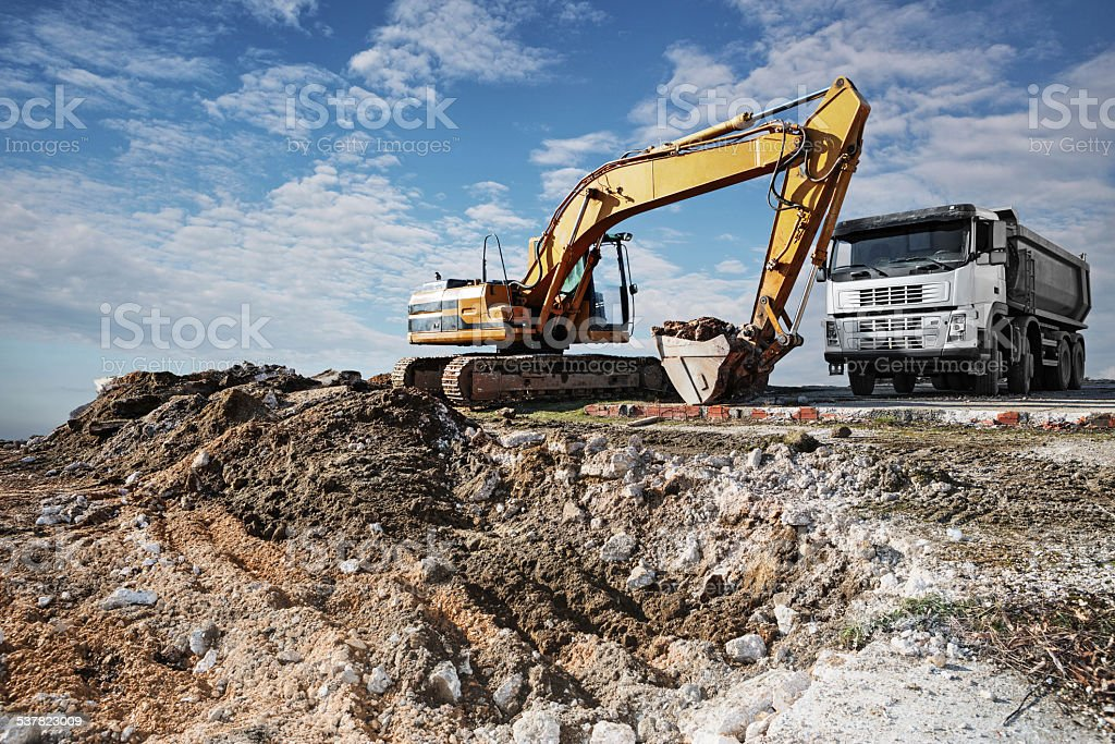 Excavator and truck on a construction site stock photo