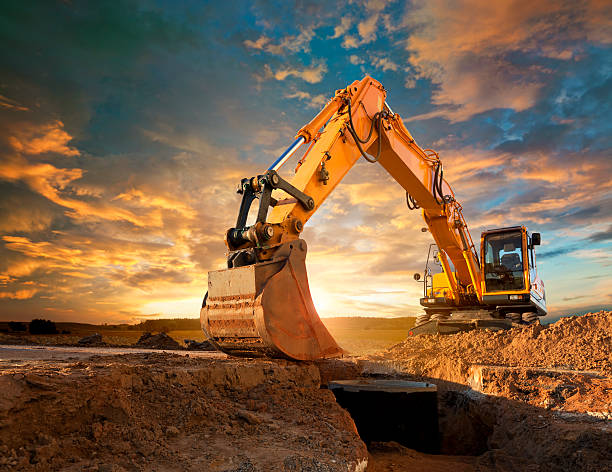 Excavator at a construction site against the setting sun. Excavator at Construction Site construction machinery stock pictures, royalty-free photos & images