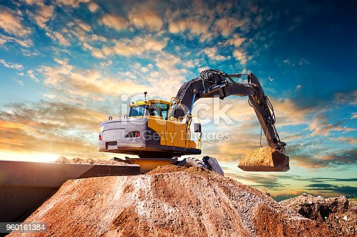 Excavator at a construction site against the setting sun. High quality image. Earth mover digs down. Orange track machine standing idle on a building construction site.