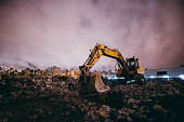 Excavator standing at a construction site on a dark night. It's standing on bricks and rubble of the old building. There's new buildings in the background.