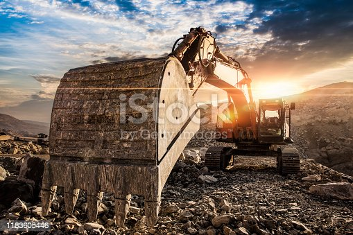 Excavator at construction site against sunset