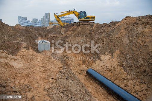 Excavator during laying drain pipes and concrete manholes for stormwater system. Connecting trench drain to concrete manhole at construction site. Construct stormwater and underground utilities