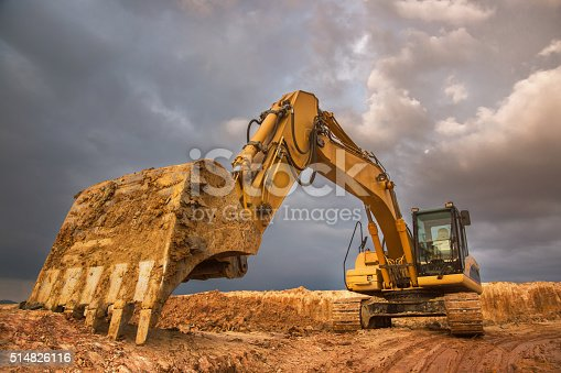 Big excavator with dramatic sky at sunset