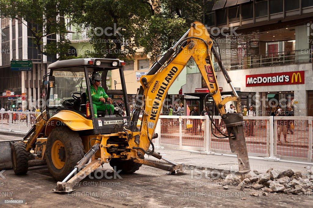 Excavator breaking asphalt stock photo